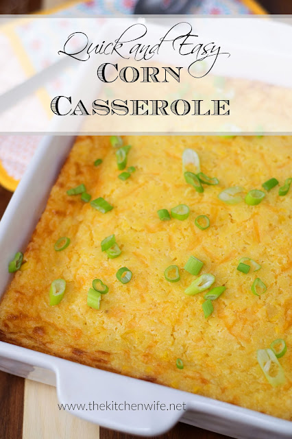 The corn casserole in a white baking dish on the counter with the title above it.