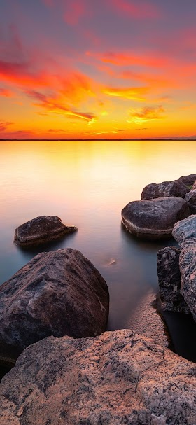 Orange sunset over calm body of water wallpaper