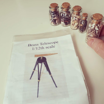 1/12 scale brass telescope kit next to five small jars of tiny shells. A hand is picking up one of the jars.