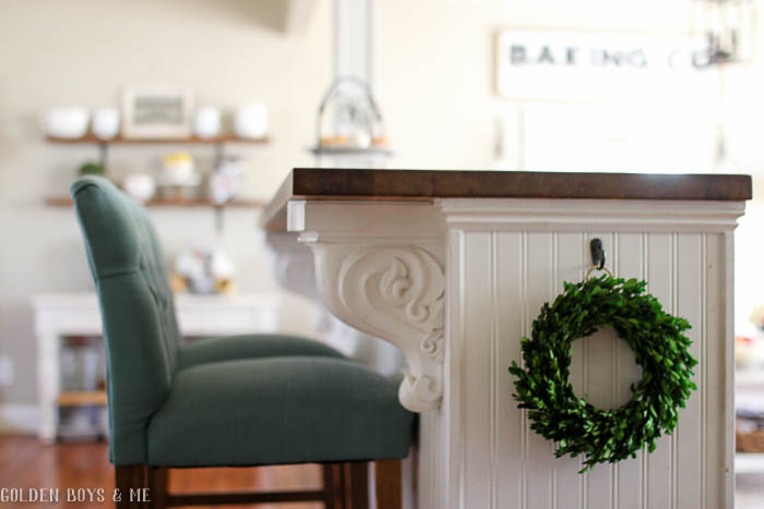 Small boxwood wreath on side of DIY kitchen island with bead board and butcher block