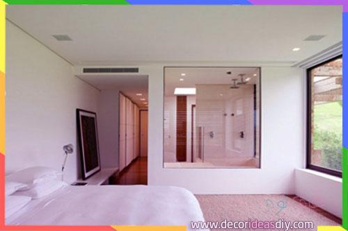 اضاءة كبيرة داخل غرف نوم مع حمامات من الزجاج