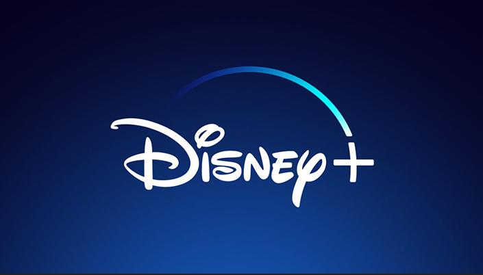 Imagem: Fundo azul escuro. Na parte superior da imagem a cor é mais forte e na inferior é levemente desbotada. No centro a logo da Disney em branco com o arco da magia em azul que termina no símbolo de +, também em branco.