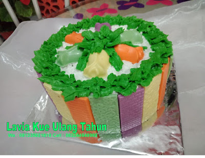 Cake tart coklat warna-warni dengan buah dan daun segar