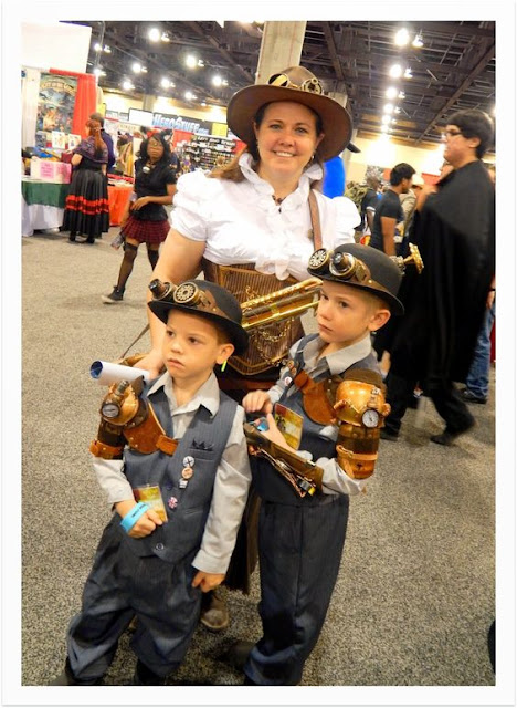 Woman dressed in Steampunk clothing along with her children. Sons and mom are dressed in victorian steampunk fashion. Steampunk cosplay for kids and families