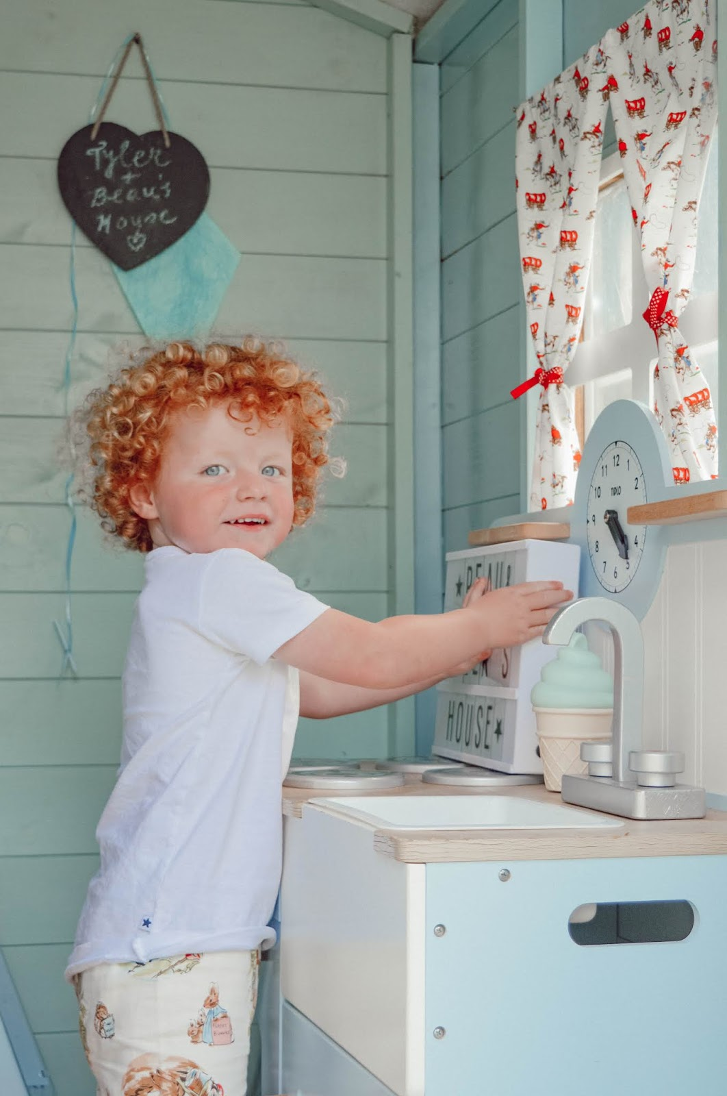 A child playing with a toy kitchen in a playhouse