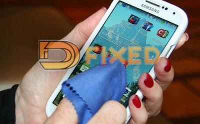 bersihkan layar HP untuk mengatasi touchscreen ghost touch