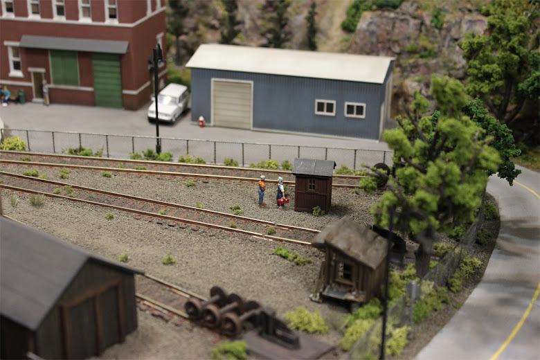 Two train mechanics chat outside of a small shed in a gravel railyard between two spur tracks