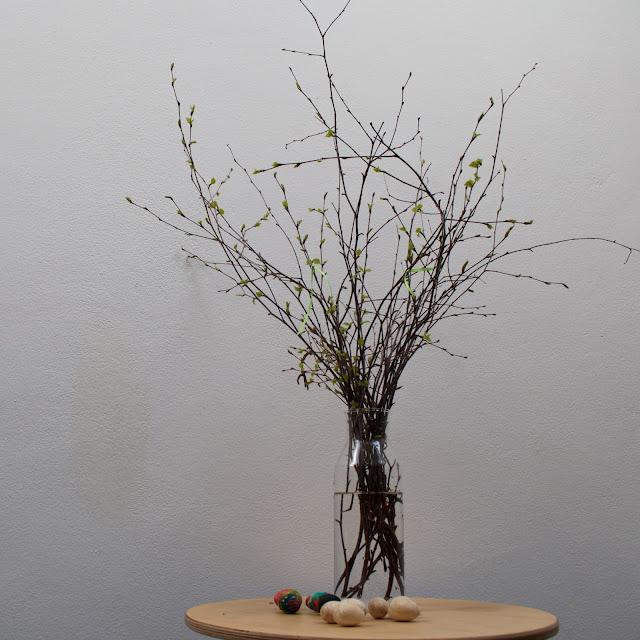 Velikonoce a velikonoční výzdoba - březové větvičky se zelenou stuhou, dřevěná vejce malovaná dětmi barvami.