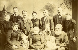 Group of men, women, and children posing for a family portrait