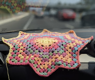 Unfinished baby blanket in pastel colours rest on a dashboard