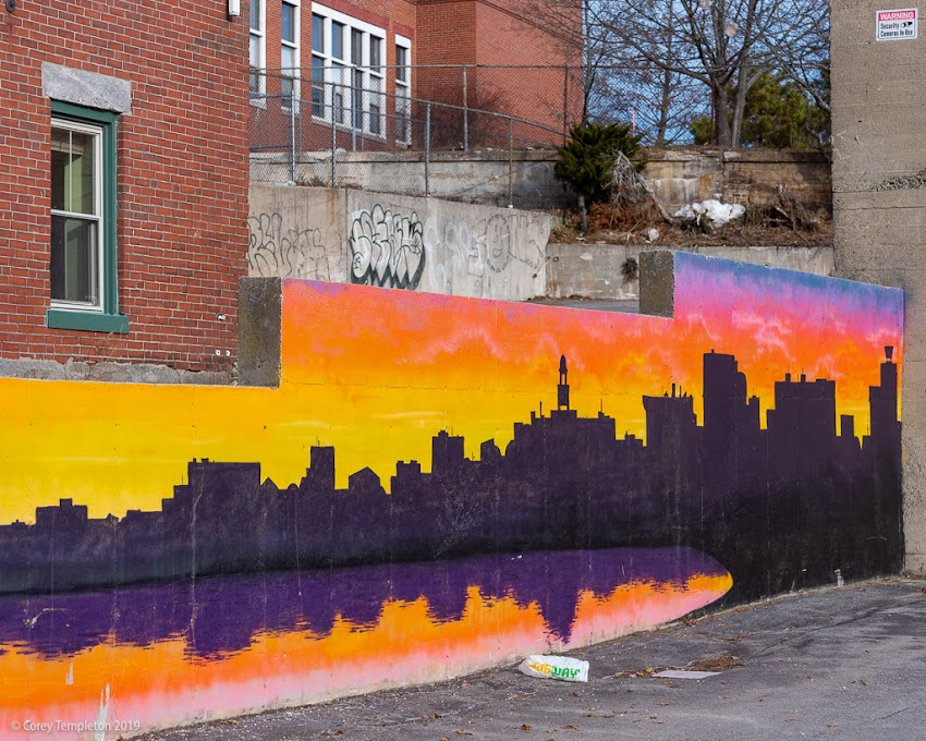 December 2019 photo by Corey Templeton. Portland, Maine. The Portland skyline featured on a colorful mural at India & Federal Streets. It's a pretty accurate portrayal of watching the sun rise from across Back Cove.