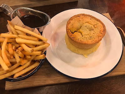 a pie on a white plater with a bowl of chips and a metal gravy jug on a plank of wood