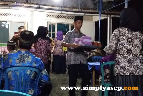 """MAKAN MALAM : Denga sigap para """"pramugari"""" ini membagikan kotak kotak makanan kepada para jamaah   Tadinya sempat dikira ada peragaan busana. Foto Asep Haryono"""