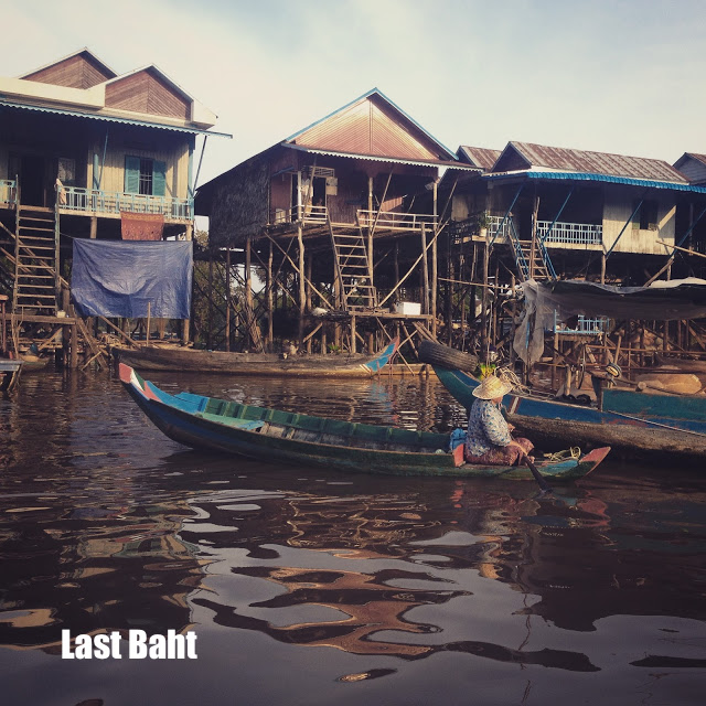 a local villages on a wooden boat passing wooden houses on stilts in the lake at Siem Reap, Cambodia
