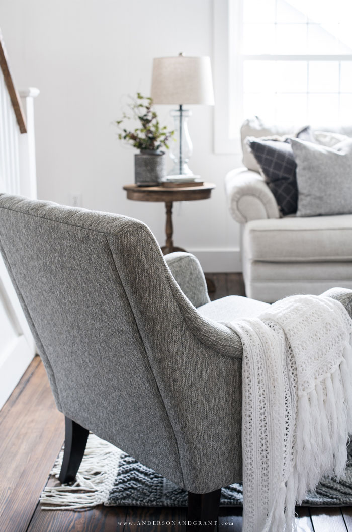 Back of a gray accent chair with white throw