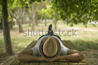 man lying below a tree (enjoying in tree's shade)