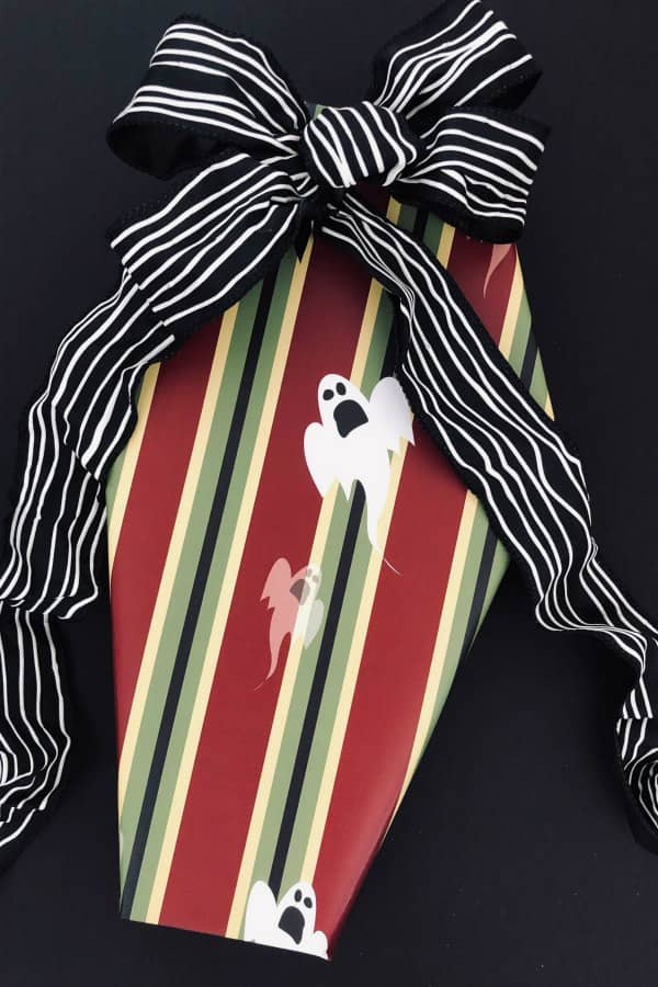 Halloween gift in shape of coffin wrapped in striped ghost paper with black and white striped ribbon and bow