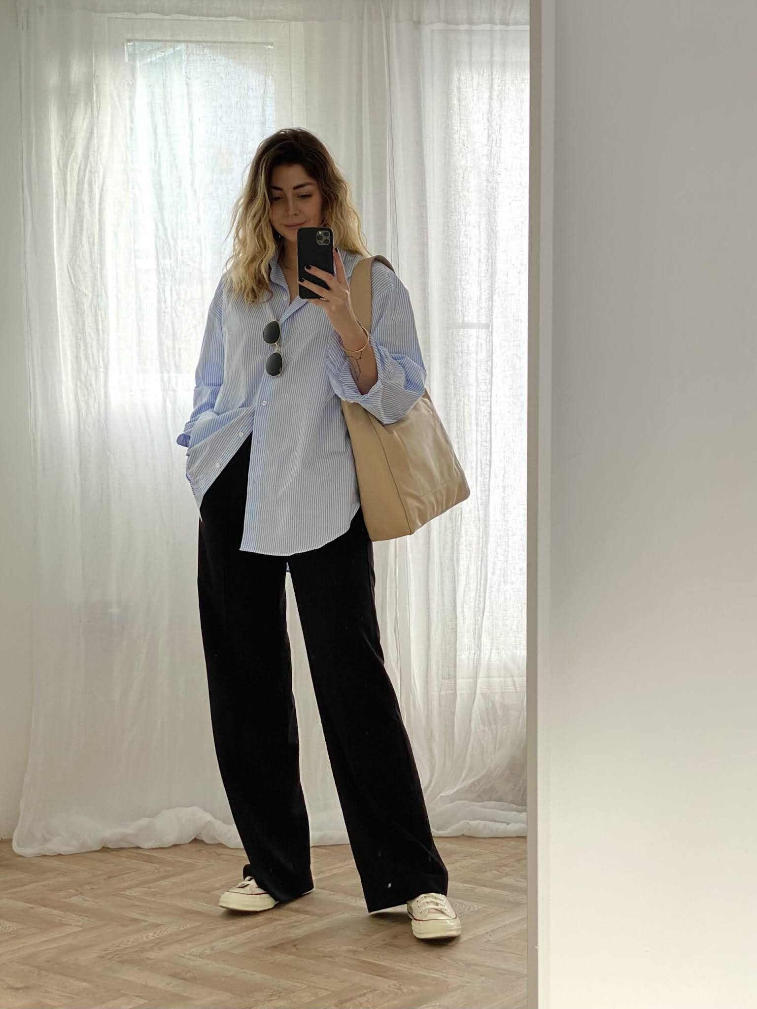 A Cool Weekend-Ready Look for Running Errands — Emma Hill in a blue striped button-down shirt, beige tote, baggy black pants, and white Converse sneakers