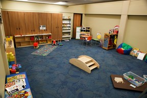 a room with blue carpet and wooden panel walls containing many low bookshelves full of books and toys, plus a few toys scattered on the floor in the playroom at the Sioux Falls branch of the Siouxland Public Libraries