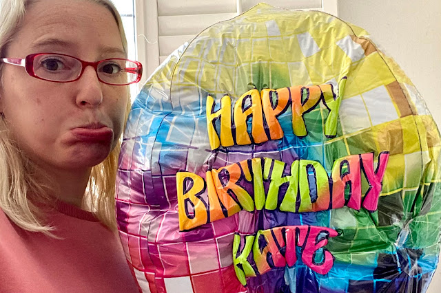 me pulling a sad face while holding a deflated multi coloured disco ball balloon with Happy Birthday Kate on it