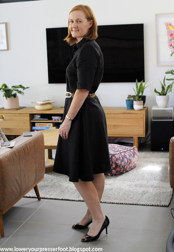 side view of a lady posing in a black shirt dress in a lounge room