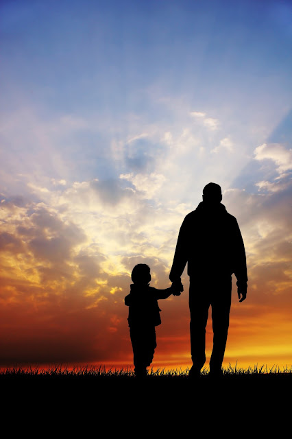Image of a dad walking with a young female child in a field at sunset