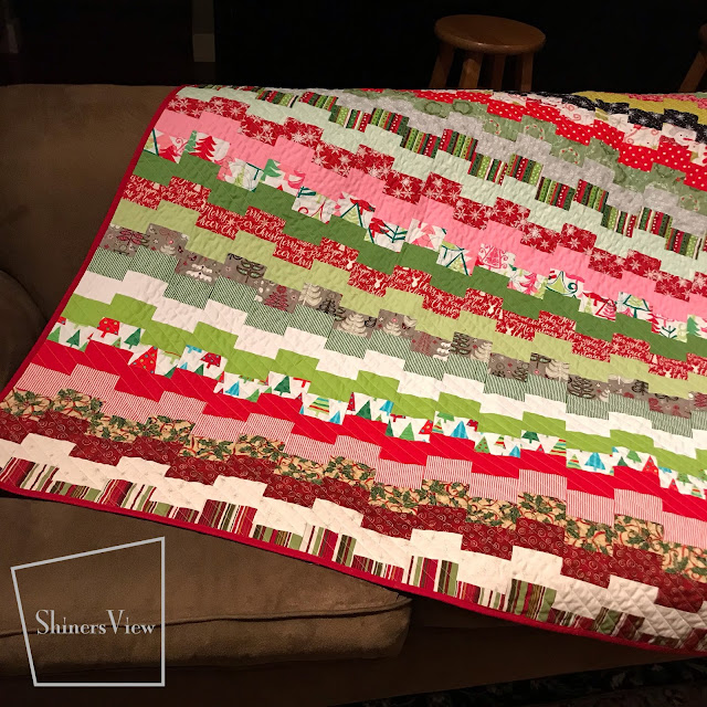 multicolored christmas quilt spread on a brown couch