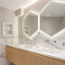 Banheiro branco com espelhos hexagonais retroiluminados e gabinete de madeira!