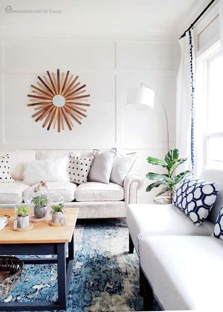white and blue living room with board and batten and sunburst mirror
