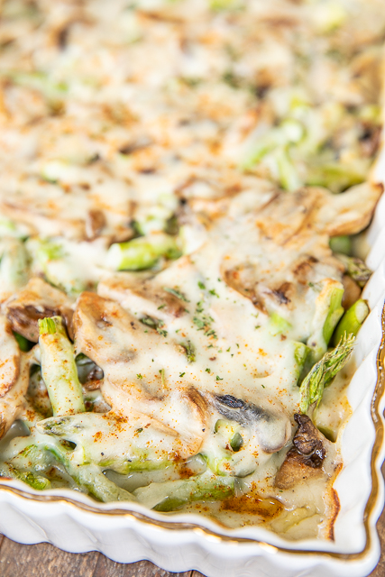 baked cheesy asparagus and mushrooms in casserole dish