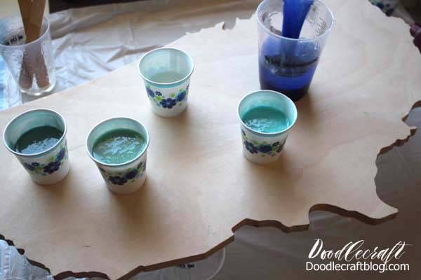 Mixing the paint into the resin for an Ocean Resin Pour on USA Cutout DIY tutorial to make home decor look like the waves of the ocean in ombre shades of blue.