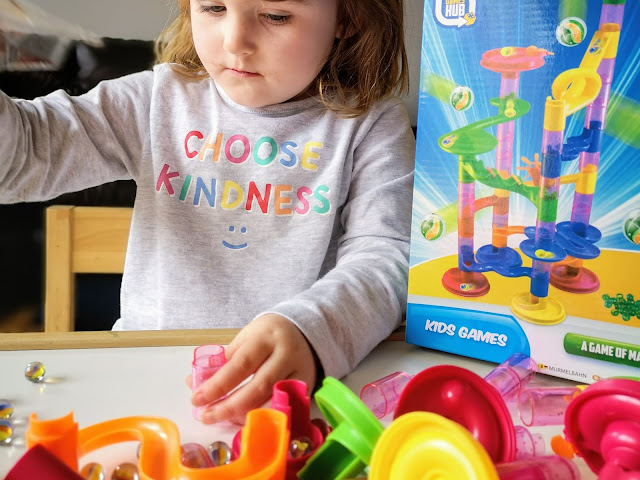 Image of a young girl in t shirt that reads 'choose kindness' in rainbow colours. She is playing with a marble run toy that consists of several multicoloured tubes, she is building them into a tower. There are slides and spinning attachments strewn across the table that can be added to the tower. To the right of the girl is the box that the marble run comes in. The front of the box shows the completed marble run.