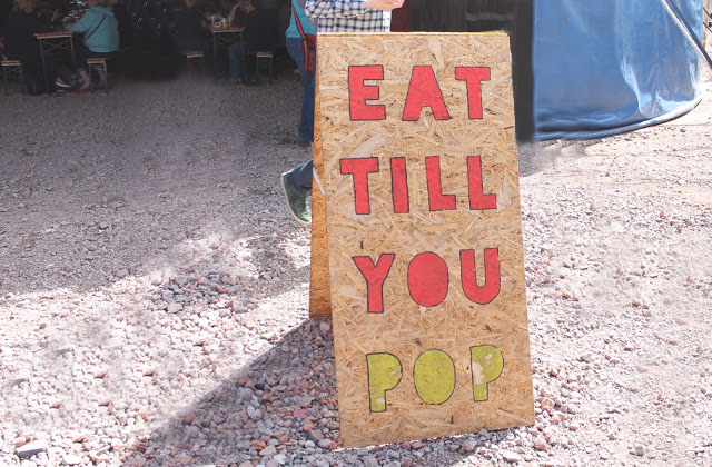 colourful corkboard sign at street food circus reading eat till you pop