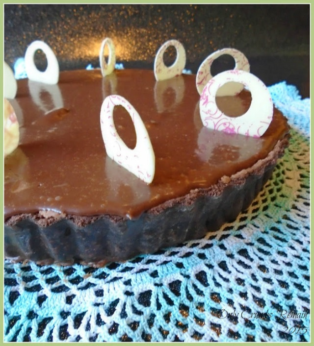 A triple chocolate tart, with a chocolate pastry case, mango cream, chocolate mousse made with aquafaba, chocolate glaze and white chocolate decorations.