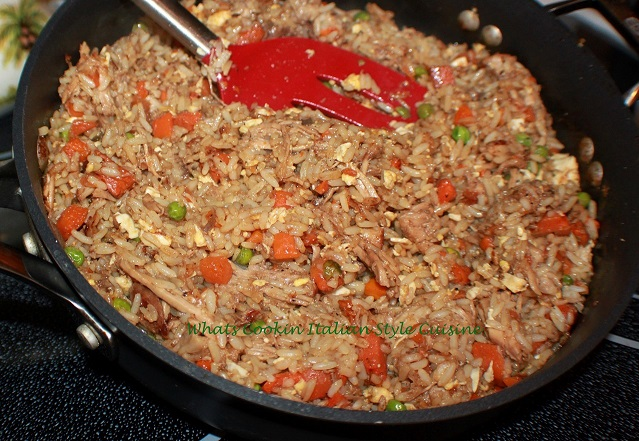This is how to make stir fried rice Asian style rice with peas and carrots with scrambled eggs in a frying pan