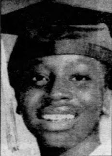 A headshot of a young, smiling Black girl wearing a graduation cap