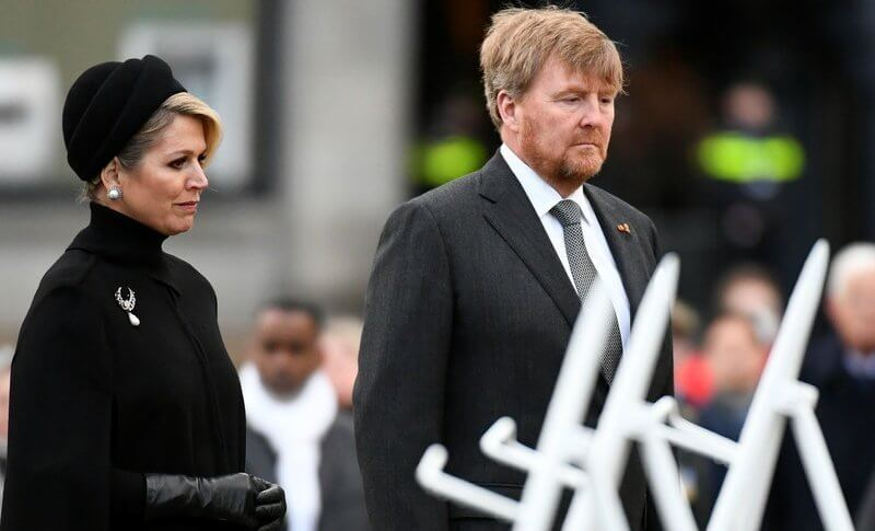 Queen Maxima wore a black wool high collar cape coat. Black leather handbag. Pearl drop earrings and diamond brooch. Gripoix earrings