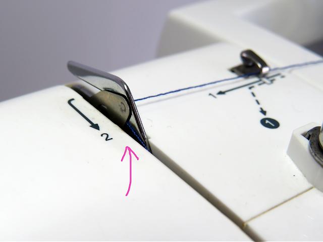 Hilo pasando por el punto dos del enhebrado superior de la máquina de coser