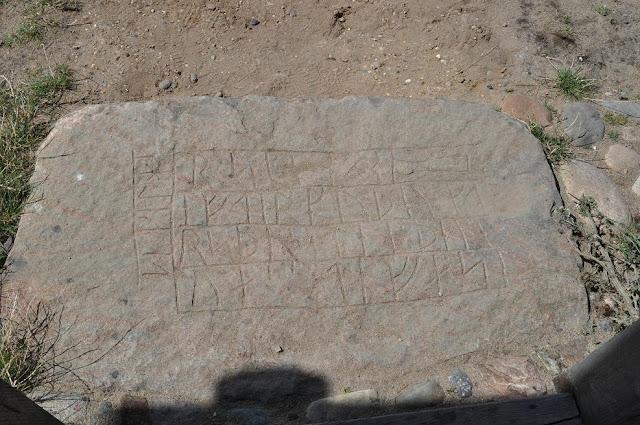 Rekonstrukcja kościoła słupowego w skansenie archeologicznym Bork Vikingehavn  - kamień runiczny wkopany jako próg