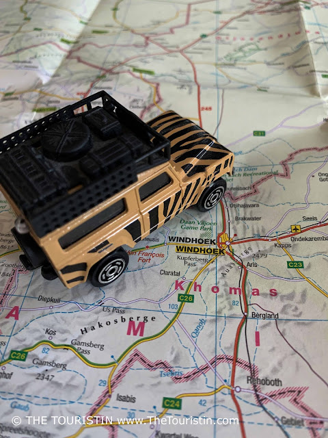 A beige and black painted toy Land Rover on a paper map next to the words Windhoek.