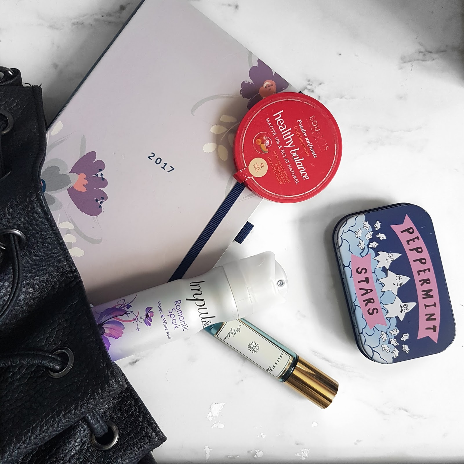 Assortment of beauty products spilling out of a handbag