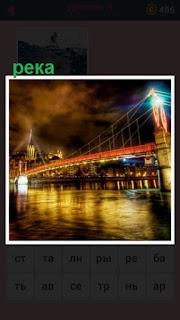 освещенный мост огнями над рекой стоит