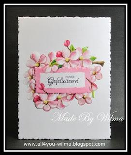 Een felicitatiekaartje met allemaal bloemen rondom een tekststempel. A birthday card with flowers all around a text stamp.