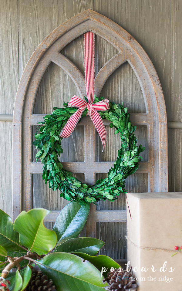 preserved boxwood wreath with red striped ribbon on arched wooden cathedral window frame