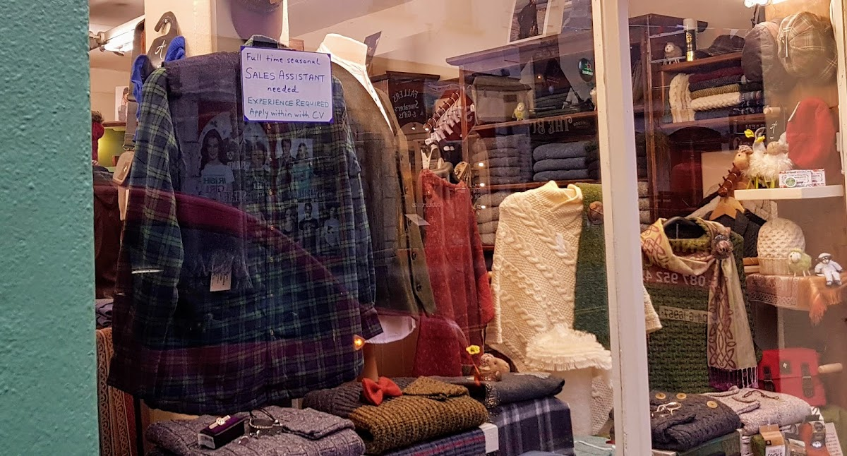 show window with job-available sign and a display of woollen clothing items, including a blue and green checked shirt and kintted jumpers