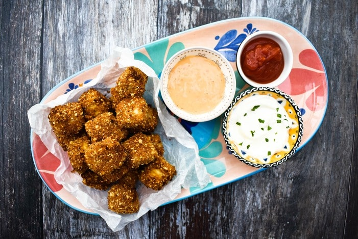Harissa Popcorn Tofu on a platter with a trio of dips