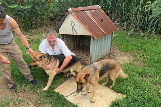 Michael Farmer seu cão Rocky e outro cão posam pra foto em frente a casa atingida pela rocha espacial