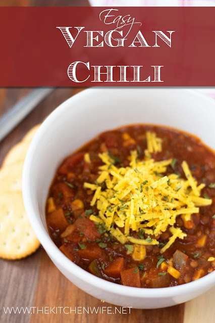 A white bowl of the perfect vegan chili, topped with vegan cheese, and crackers on the side.
