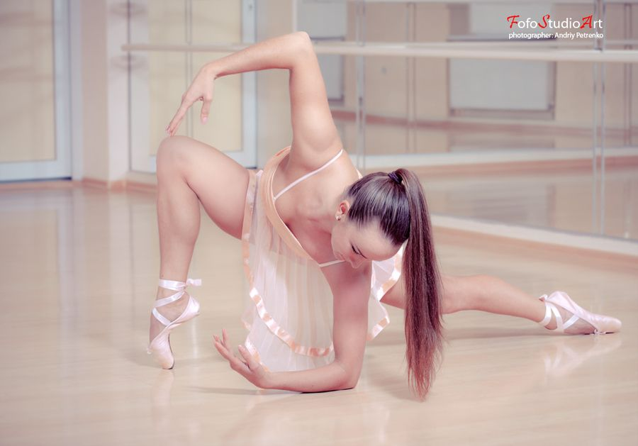 Ballerina in pink dress а against studio background
