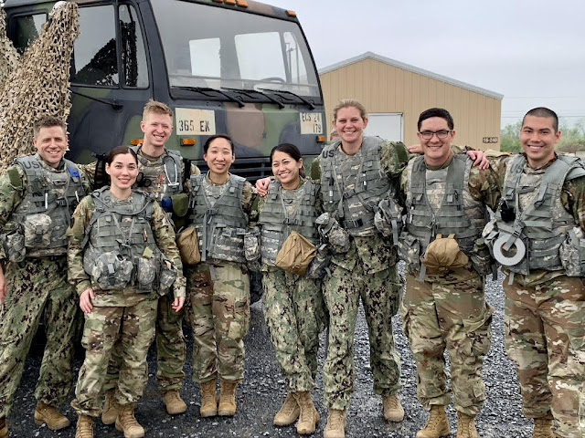 A group of students in camouflage. There is a camouflage truck behind them.